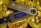 crypto wallet ledger nano s lying on golden bitcoin coins